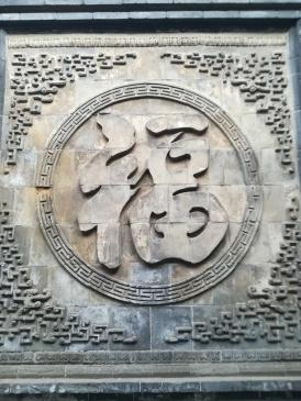 """Ein, oder das (?), Schriftzeichen für """"Glück"""" an der Wand einer alten Bank - am Tag vor dem neuen Jahr kann es kein Zufall sein, dass ich es entdecke und mir auch noch erklärt wird, was es bedeutet. So verschicke ich das Bild Tags darauf bei WeChat als Neujahrsgruß an all meine chinesischen WeChat-Freunde und bekomme höchst erstaunte und vor allem höchst erfreute Kommentare zurück."""