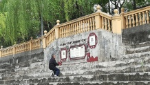 Beim Flussspaziergang in Guang Yu An: ein alter Mann sitzt auf seinem Schemel und liest auf die Mauer gepinselte Texte.